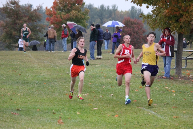 Jon (UXC runner on the left) ran a gutsy race in the rain at the county meet.  He ran the entire race in a pack of 3 runners in the front, fighting for the top spot.